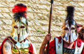 two men in face helmets and ancient military costumes