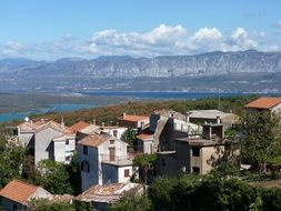 old village at sea in view of mountains, croatia
