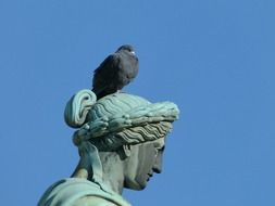 pigeon sits on head of bronze sculpture