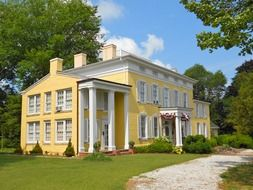 old yellow mansion with columns in summer park, usa, delaware