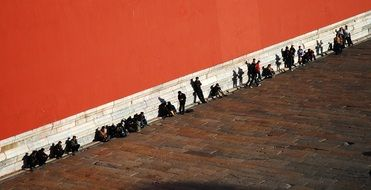 people resting at red wall of palace museum, china, beijing