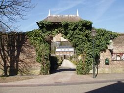 stone wall with gateway in front of castle, netherlands, amstenrade