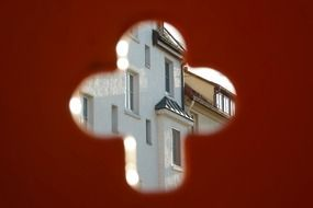 House facade through the hole in a red wall