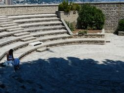 lonely woman sits on stone bench in open air theatre, monaco, fort antoine
