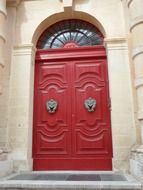 old wooden red door under arched window