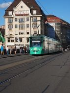 green tram and people on middle rhine bridge in old city, switzerland, basel