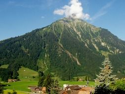 cloud at top of green mountain, scenic summer landscape, switzerland