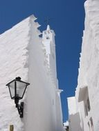 vintage lantern on wall of white lime church, spain, menorca