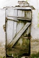 old wooden door in damaged wall