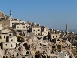 minarets on mountain side among tuff stone dwellings, turkey, uchisar