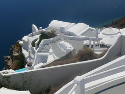 white apartment terrace on cliff at blue sea, greece, santorini, caldera