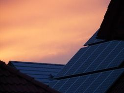 sunset over solar panels on a roof