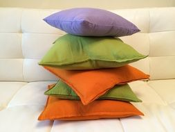 stack of colorful pillows on sofa