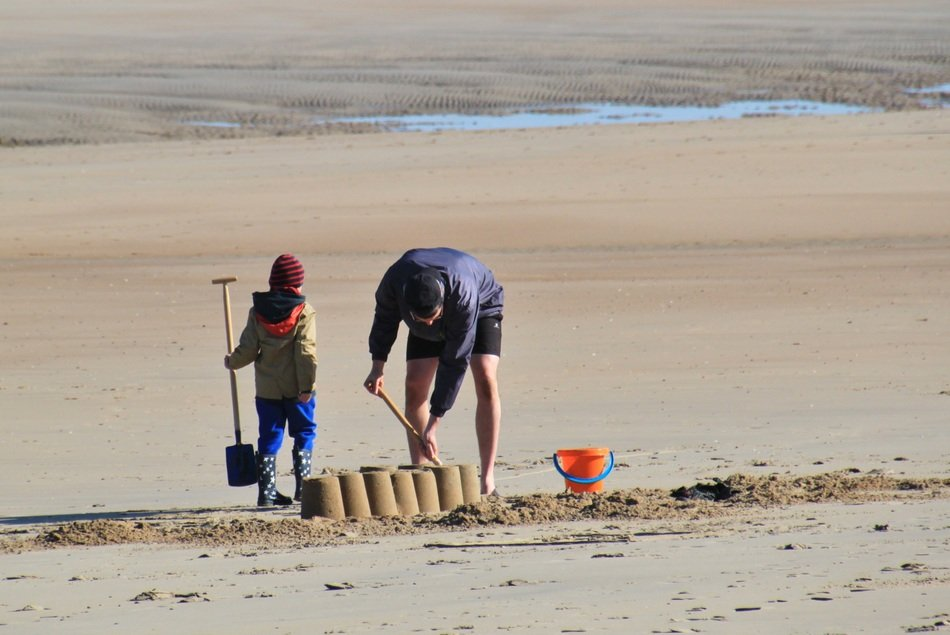 man and child boy with shovels building sand castle on beach