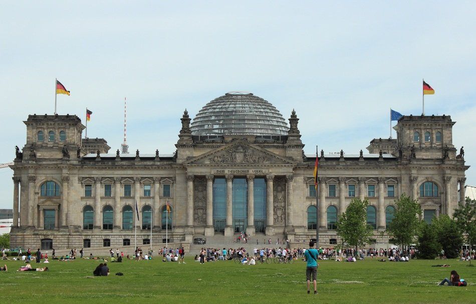 people resting on lawn at bundestag building, germany, berlin