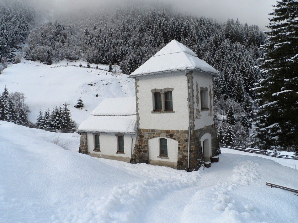 small old chapel building at forest, snowy winter landscape, austria
