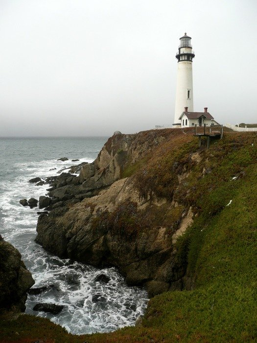Pigeon Point Lighthouse on rocky coast at clouds, usa, california