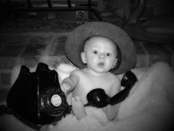 child with old telephone in black and white image