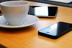 a cup of coffee in the office on the background of the smartphones