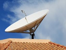 parabolic antenna on clay tile roof at sky