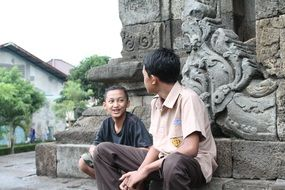 indonesian boys chatting at ancient wall