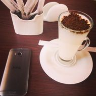 coffee with chocolate and a mobile phone on a table in a cafe
