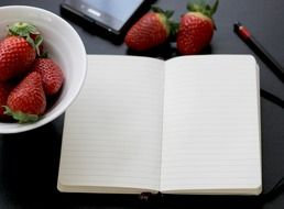 clean notebook and a plate of strawberries