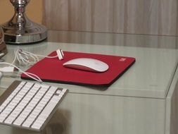 white keyboard, white mouse and red computer pad on the table