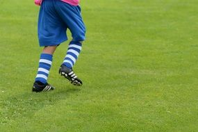 young boy playing football in kick shoes