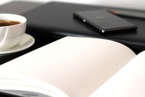 a cup of coffee, a mobile phone and an open notebook