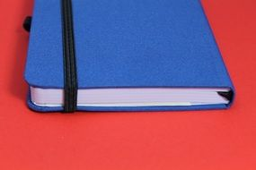 blue notebook on a red table