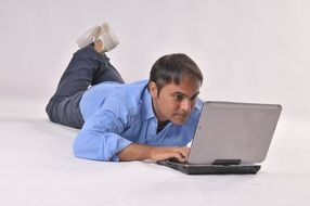 man lying on the ground working at a laptop