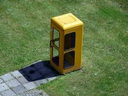 yellow phone booth on the lawn