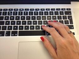 hand with red manicure on a laptop keyboard
