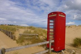 red vintage phone booth on sand beach