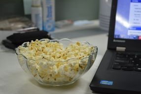 popcorn in bowl at computer on desk