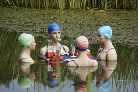 Women in swimming caps communicate in the pond