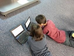 children with laptops on the floor in the room