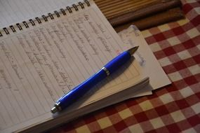 write in a notebook and a blue pen