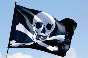 Black and white Pirate flag floating in the wind at blue sky background with white clouds