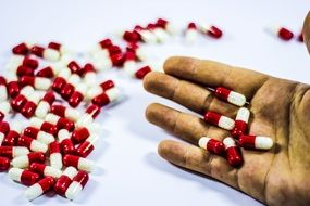 Capsules with medicine in hand on the background of other capsules