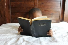 child reading bible bed african