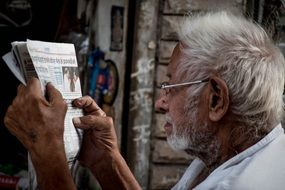 old man in glasses reading newspaper
