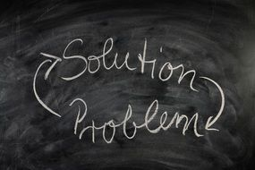 inscription on a blackboard about problem solutions