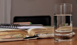 glass with water in front of open book on desk