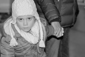 little girl in white cap view winter