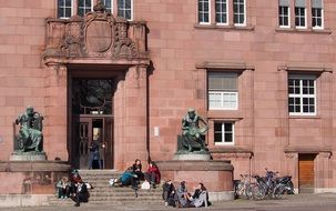 students sit on steps at entrance to university building, germany, freiburg