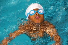 child in swimming glasses in the pool