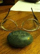 stone with the inscription wisdom and glasses on the table
