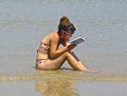 girl with a book in the water on the beach